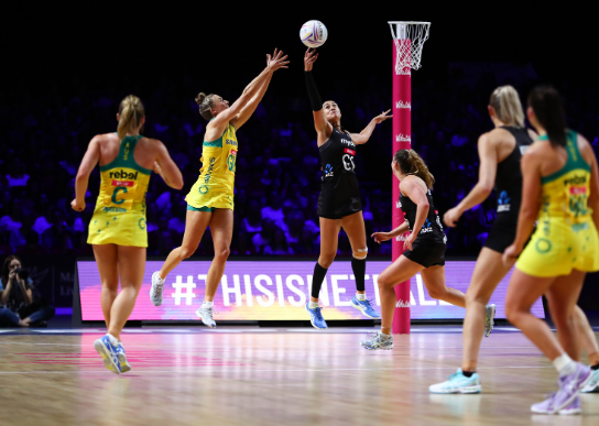 Australia and the New Zealand netball teams throw a ball into the hoop