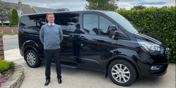Andy stands in front of a black van - part of the ADM Executive Travel Fleet