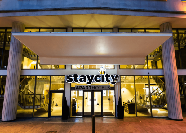 The exterior of staycity aparthotel. A glass frontage and black staycity sign